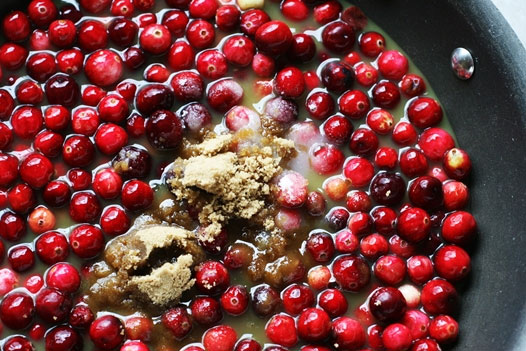 fresh cranberries sauce cooking in a pan with brown sugar